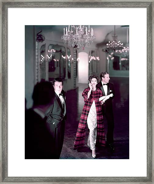 Model In Silver Dress Escorted By A Gentleman Framed Print