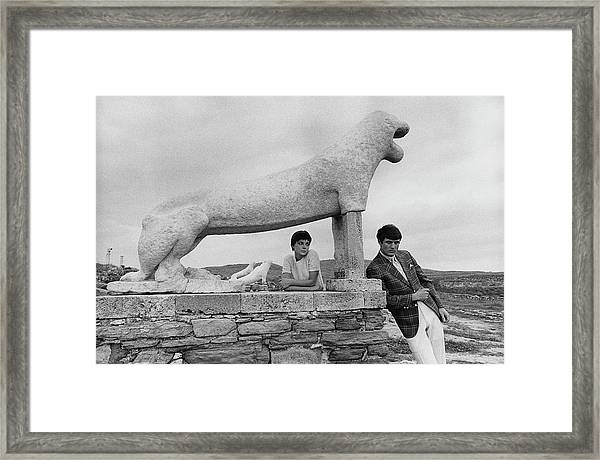 Models Posing By A Sculpture Of A Lion Framed Print