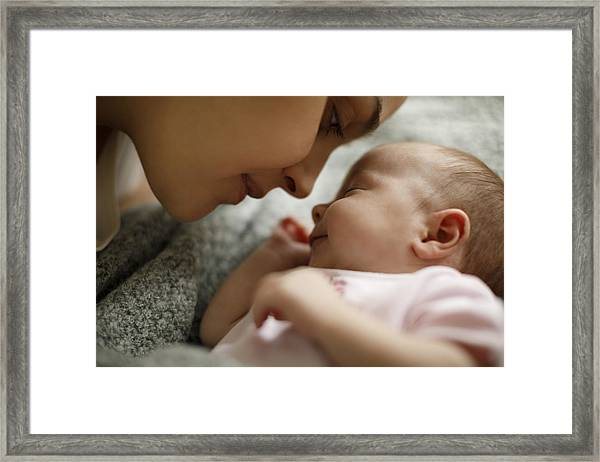 Mother And Baby Playing In The Bed Framed Print by Damircudic