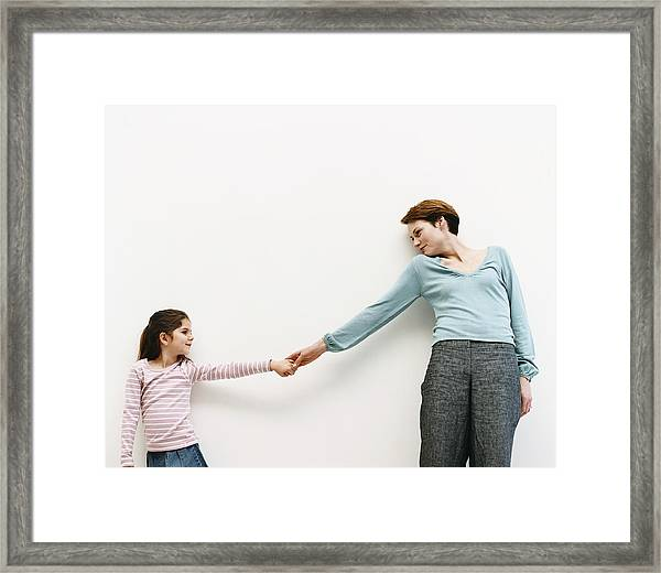 Mother And Her Daughter Stand By A Wall, Reaching Out And Holding Hands Framed Print by Dylan Ellis