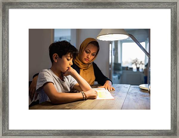 Mother And Son Reading Book Under Illuminated Desk Lamp At Home Framed Print by Maskot