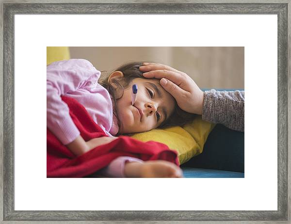 Mother Checking On Sick Daughter Laying In Bed Framed Print by Ridvan_celik
