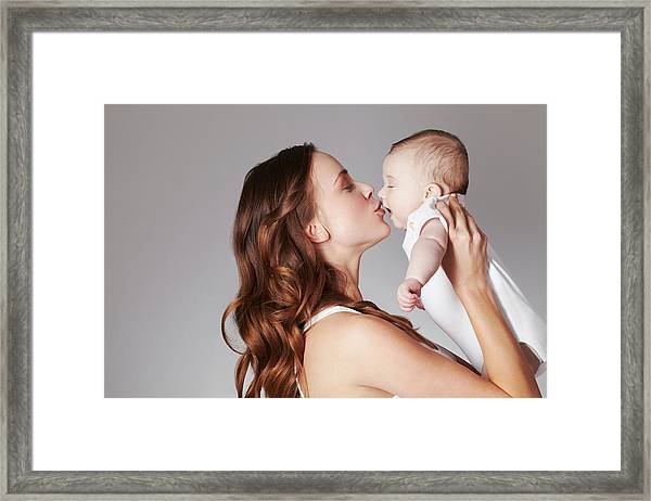 Mother Kissing Baby Daughter Framed Print by Emma Kim