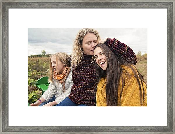 Mother Kissing Teenage Daughter Strolling In Trailer In Field. Framed Print by Martinedoucet