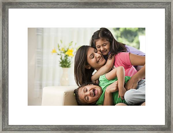 Mother With Daughters (6-7) Sitting On Sofa Framed Print by ImagesBazaar