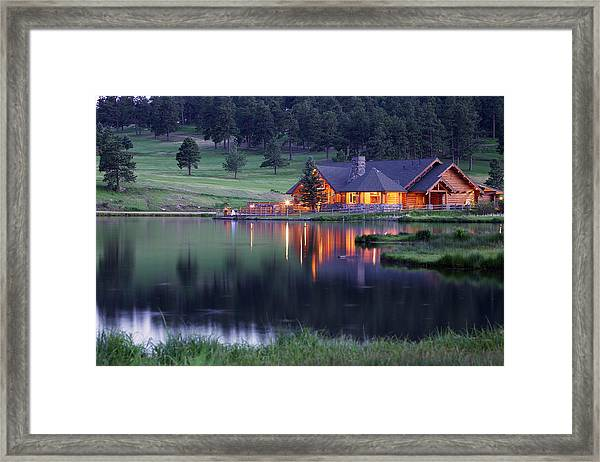 Mountain Lodge Reflecting In Lake At Framed Print