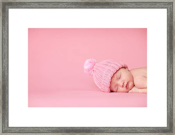 Newborn Baby Girl Sleeping Peacefully On Pink Background Framed Print by Ideabug