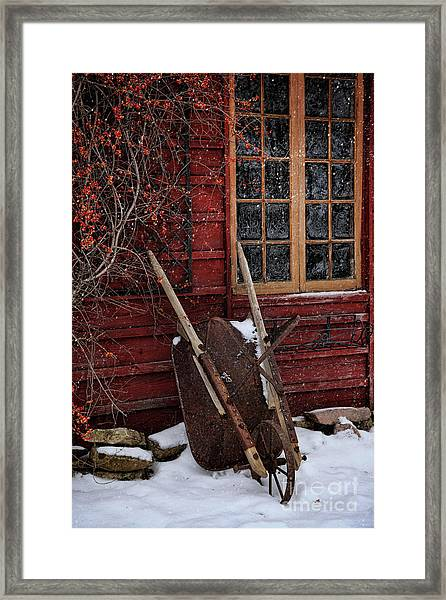 Old Wheelbarrow Leaning Against Barn In Winter Framed Print