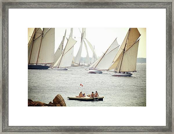 People Sit On A Floating Dock And Watch Framed Print
