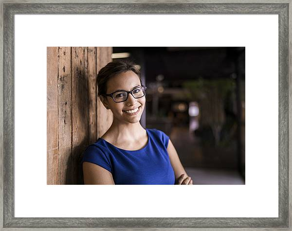 Portrait Of Confident Businesswoman Against Wooden Wall Framed Print by Portra
