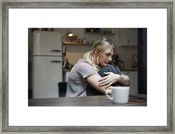 Portrait Of Pensive Woman Sitting At Table In The Kitchen Framed Print by Westend61