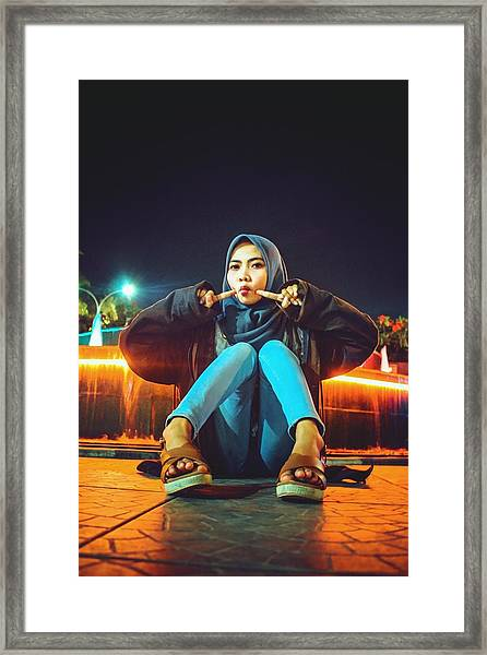 Portrait Of Young Woman Wearing Hijab While Sitting On Footpath At Night Framed Print by Ilham Adhi Kusuma / EyeEm