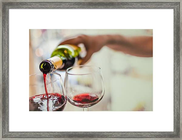 Pouring Red Wine In Glasses Framed Print by Instants