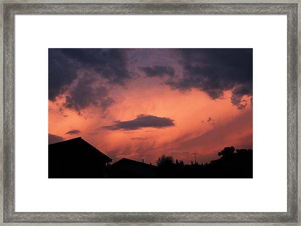 Purple Clouds Gather In A Pink Sky Above Dark Houses Framed Print by Photodisc