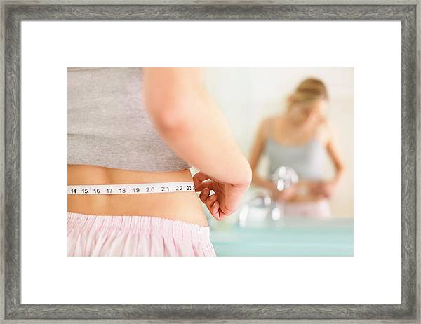 Rear View Of Woman Measuring Waist With Mirror Reflection Framed Print by GlobalStock