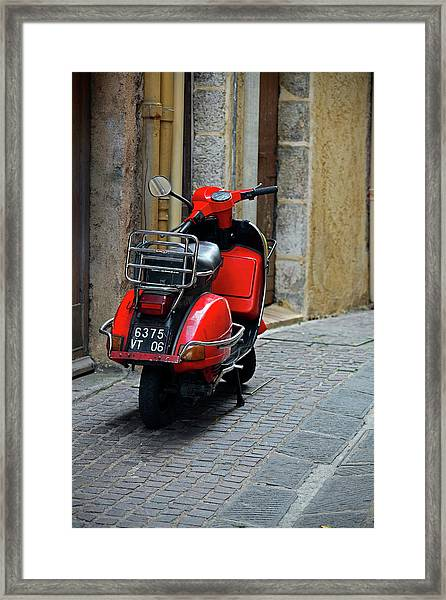 Red Vespa Scooter Parked In Sidestreet Framed Print
