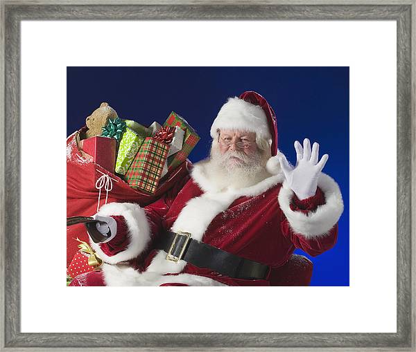 Santa Claus Next To Bag Of Toys Framed Print by Tetra Images