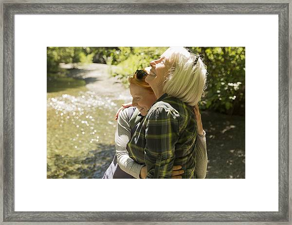 Senior Woman And Daughter Hiking Hugging By River Framed Print by Compassionate Eye Foundation/Steven Errico