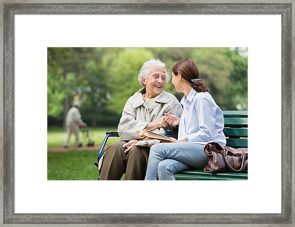 Senior Woman With Caregiver In The Park Framed Print by FredFroese