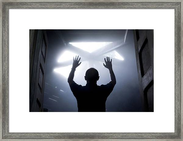 Silhouette Of A Man With Raised Hands Against Light Coming From Above. Framed Print by Maciej Toporowicz, NYC
