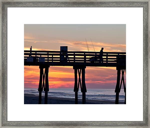 Silhouetted Fisherman On Ocean Pier At Sunrise Framed Print