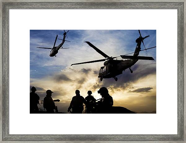 Silhouettes Of Soldiers During Military Mission At Dusk Framed Print by Guvendemir