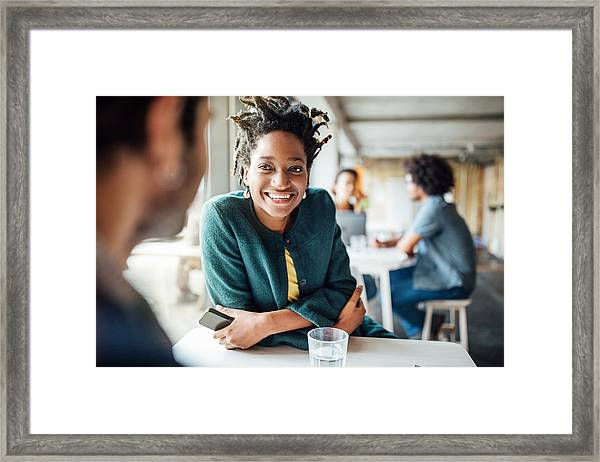 Smiling Businesswoman Sitting With Colleague In Cafeteria Framed Print by Luis Alvarez