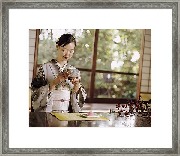 Smiling Woman Drinking Tea During A Japanese Tea Ceremony Framed Print by Digital Vision.