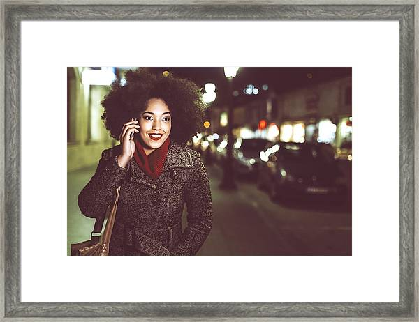 Smiling Young Woman Using Phone On Street By Night Framed Print by Portishead1