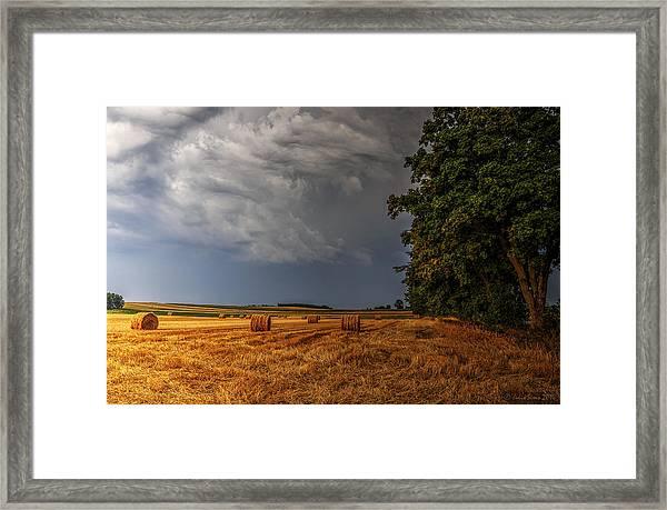 Storm Clouds Over Harvested Field In Poland Framed Print