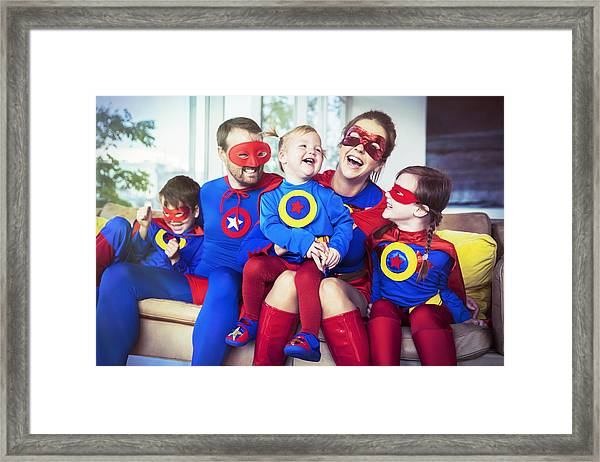 Superhero Family Laughing On Sofa Framed Print by Robert Daly