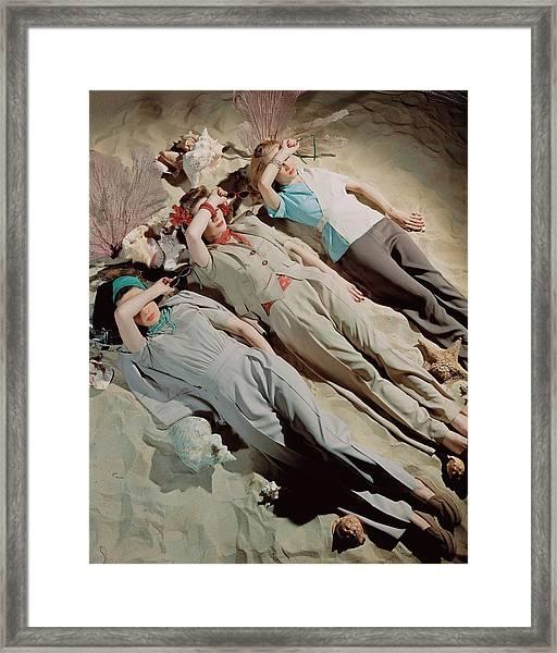Three Models Lying Down On Sand Framed Print by John Rawlings