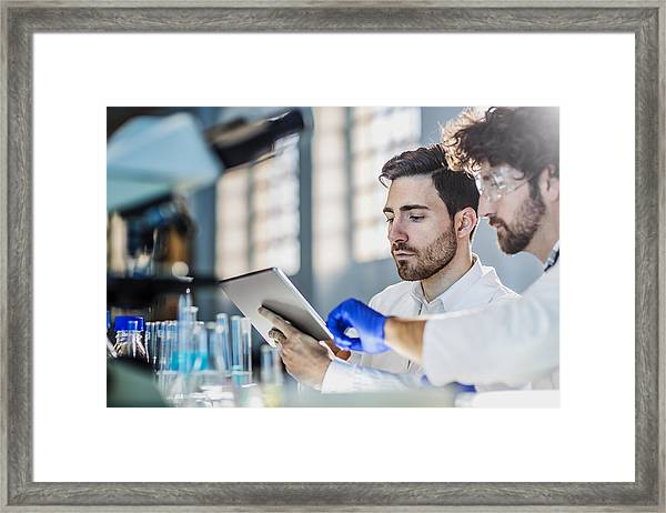 Two Scientist Using Digital Tablet In Laboratory Framed Print by Poba