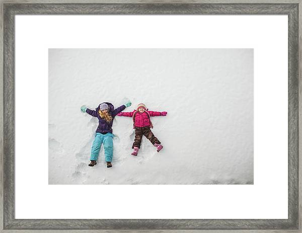 Two Sisters Playing, Making Snow Angels Framed Print