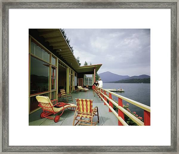 Two Women On The Deck Of A House On A Lake Framed Print