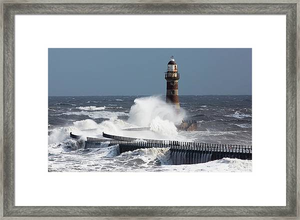 Waves Crashing Into A Lighthouse On The Framed Print
