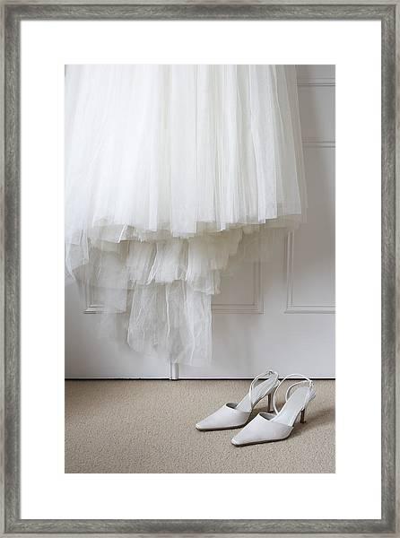 White Shoes On Floor Beneath Wedding Dress Hanging Outside Wardrobe Framed Print by Michael Blann