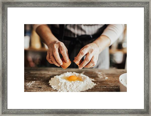 Woman Adds An Egg To The Flour Framed Print by Anchiy