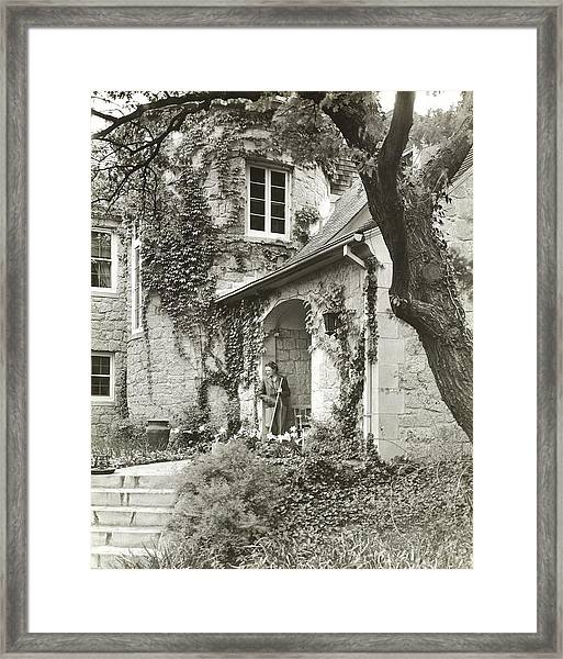 Woman In Doorway Of House Framed Print