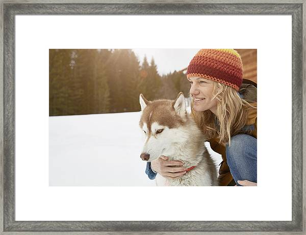 Woman Kneeling With Husky In Snow Covered Landscape, Elmau, Bavaria, Germany Framed Print by Stephen Lux