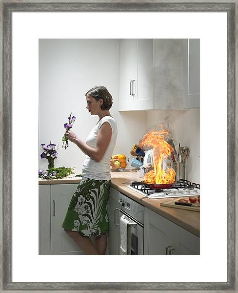 woman Leaning Against Kitchen Worktop Holding Flower, Frying Pan On Fire Behind Framed Print by Michael Blann