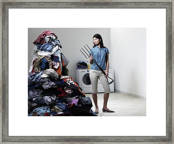Woman Next To Pile Of Laudry With Pitchfork. Framed Print by Ryan McVay