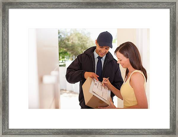 Woman Signing Box Receipt For Delivery Man Framed Print by Paul Bradbury