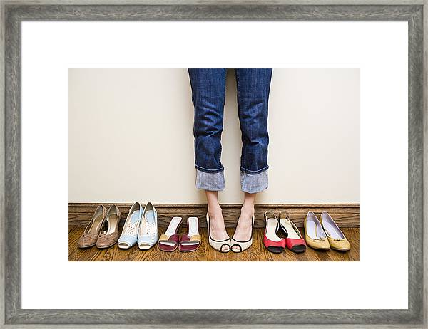 Woman Stands Wearing Heels With Her Collection Of Shoes Framed Print by Michellegibson