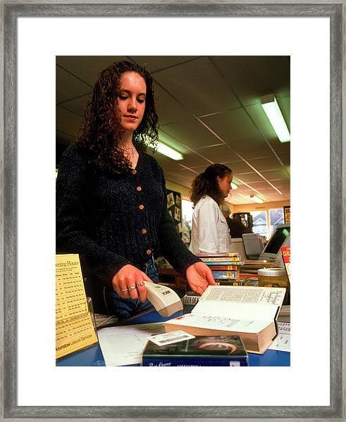 Woman Using A Bar Code Scanner In A Library Framed Print