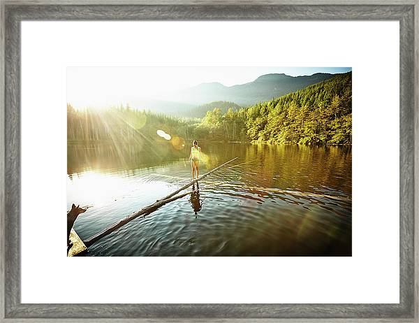 Woman Walking On Log In Alpine  Lake Framed Print by Thomas Barwick