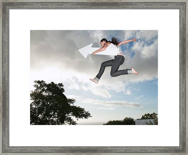 Woman With Blank Arrow Leaping Outdoors Framed Print by Robert Daly
