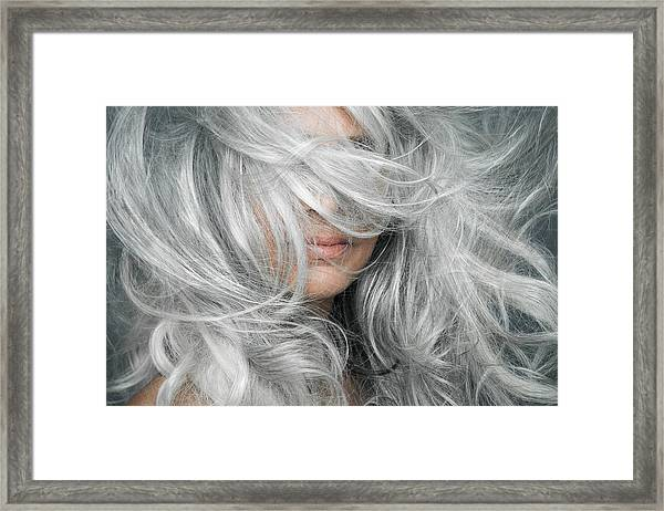 Woman With Grey Hair Blowing Across Her Face. Framed Print by Andreas Kuehn
