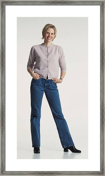 Young Beautiful Caucasion Adult Female Dressed Casually In Jeans And A Sweater Stands Smiling Confidently At The Camera Framed Print by Photodisc