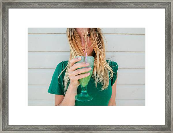 Young Blond Woman In A Green Top, Drinking Juice Framed Print by Matilda Delves